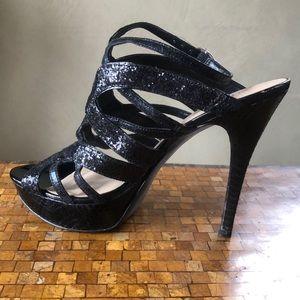 Platform front strappy black glitter heels.